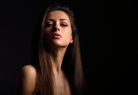 Beautiful makeup seriois woman with long hair looking sexy with half shadow on the face. Closeup portrait. Art Stock Photo