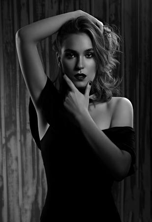 Mystische Make-up-Frau, die die lange lockige Frisur der Hand hält und Leidenschaft auf dunklem Schattenhintergrund sucht. Kunstportrait. Schwarz und weiß