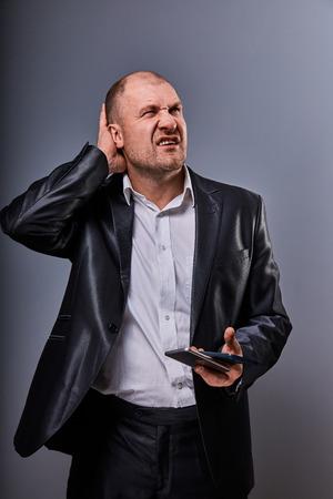 Malheureux a souligné l'homme d'affaires en colère parlant au téléphone mobile très émotif en costume de bureau sur fond gris. Portrait en gros plan