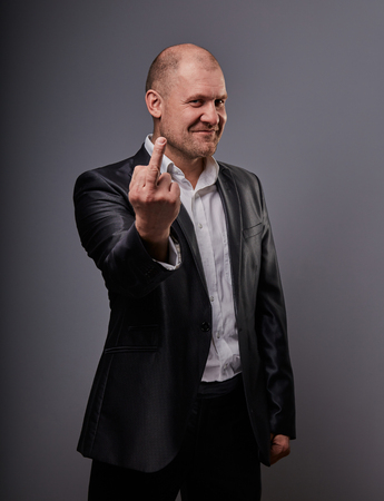 Fun comic smiling bald business man in black suit showing the finger sign on grey background. Closeup portrait