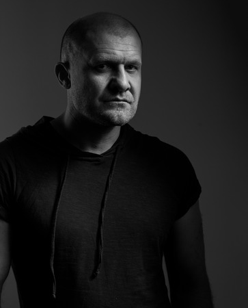 Sad angry crime man with bald head looking mystery and agressive in black shirt on dark grey background. Closeup portrait