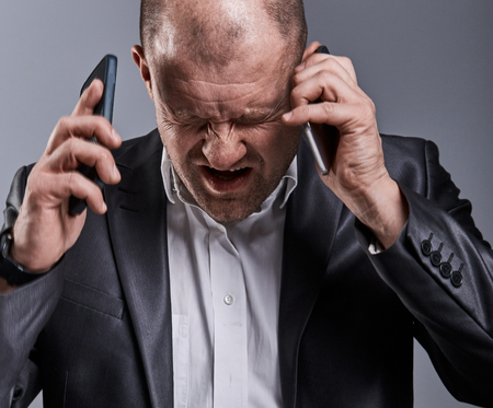 Unhappy loud crying angry business man talking on mobile phone very horrible emotions in office suit on grey studio background. Closeup contrast portrait