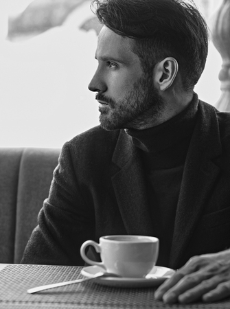 Thinking handsome man sitting in cafe and drinking cup of coffee on the breakfast. Closeup portrait. Profile view. Black and white