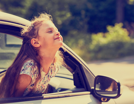 Fun happy enjoying traveling kid girl looking from the car window with open mouth on summer bright green nature background. Closeup. Little driver. Kids safety. Toned Imagens