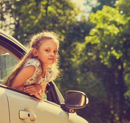 Fun happy enjoying traveling kid girl looking from the car window with open mouth on summer bright green nature background. Closeup toned summer portrait. Little driver. Kids safety. Stock Photo