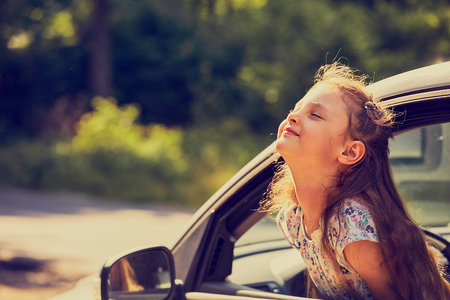 Fun happy enjoying traveling kid girl looking from the car window with open mouth on summer bright green nature background. Closeup. Little driver. Kids safety.