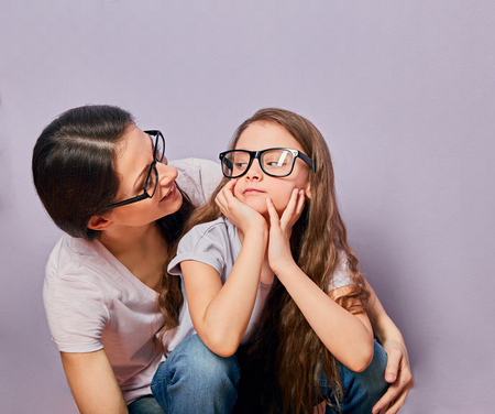 Happy smiling young casual mother looking on her cute unhappy offended thinking kid girl on violet wall background. Family in fashion eye glasses. Portrait