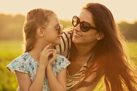 Happy fashion kid girl embracing her mother in trendy sunglasses smiling and looking on each other on nature background. Closeup