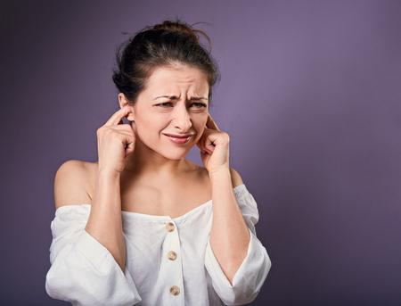 Une femme décontractée stressée et malheureuse a fermé les oreilles les doigts car elle ne veut pas entendre de sons et de bruits sur fond violet. Portrait en gros plan