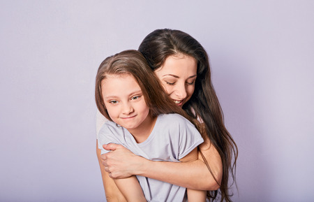 Mother and kid girl hugging with happy emotional faces on purple background with empty copy space. Closeup portrait