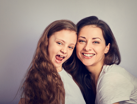 Happy mother and excited joying kid girl hugging with emotional smiling faces on purple background with empty copy space. Closeup toned portrait