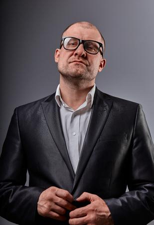 Thinking fun bald business man looking serious in eyeglasses in suit on grey background. Closeup portrait 版權商用圖片