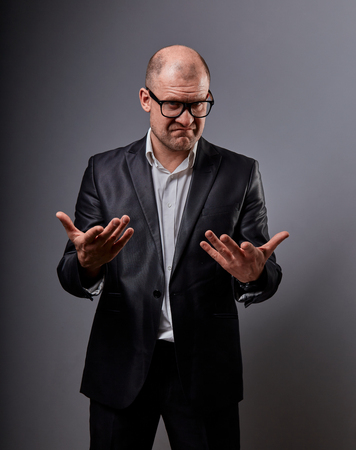 Unhappy busuness man in black suit and glasses showing the palm calling and promote sign on grey background. Closeup portrait