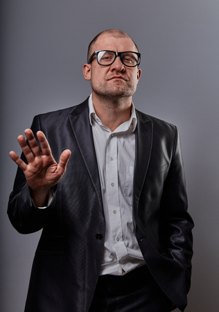 Unhappy depressed busuness man in black suit and glasses showing the palm stop sign on grey background. Closeup portrait