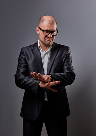 Unhappy busuness man in black suit and glasses showing the palm refusing sign on grey background. Closeup portrait