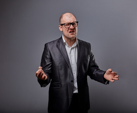Angry bald business man in black fashion eyeglasses trying to practice the yoga and crying with grimacing face on grey background. Closeup portrait