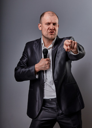 Fun emotional moving happy performer man presenting the show holding microphone in hand and showing the finger the choosing sign on grey color background. Closeup portrait Stock Photo