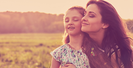 Happy enjoying mother hugging her relaxing joying kid girl and breathing fresh air on sunset bright summer background. Closeup toned color portrait