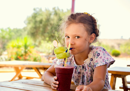 Cute smiling thinking kid girl drinking smoothie juice with fun look in summer cafe. Closeup toned portrait