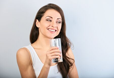 Positive happy smiling woman with healthy skin and long curly hair drinking pure water and looking up. Closeup portrait 版權商用圖片