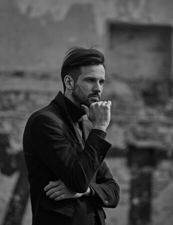 Thinking beard sad handsome male model in trouble posing in style clothing blue jacket and trousers on street wall outdoors background. Closeup portrait. Black and white