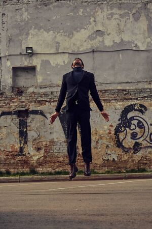Depressed lonely man jumping and wanting to fly and travel from problem. Business concept of free. Outdoor portrait Foto de archivo