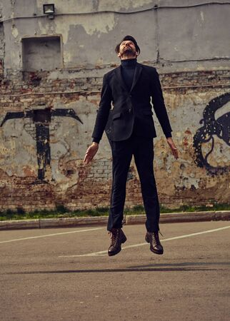 Depressed lonely man jumping and wanting to fly and travel from problem. Business concept of free. Outdoor portrait.