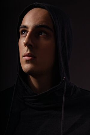 Mysterious serious man in black hoodie with hood on the head looking up on dark background. Dangerous criminal person in dark shadow.