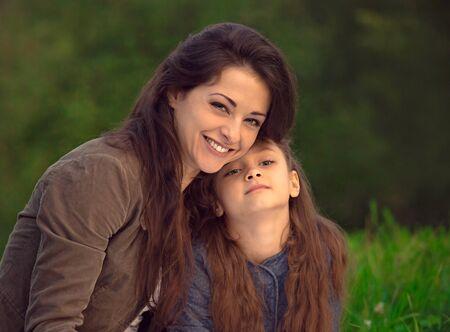 Mooie jonge lachende moeder die haar schattige lange haardochter omhelst op de zomer groen gras achtergrond. Portret van picknick ontspannende tijd Stockfoto