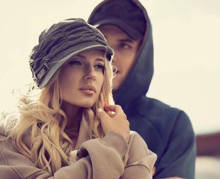 Stilish pareja caminando en modernas sudaderas con capucha y sombreros de moda en el fondo de edificios antiguos de la ciudad de otoño. Primer retrato en tonos