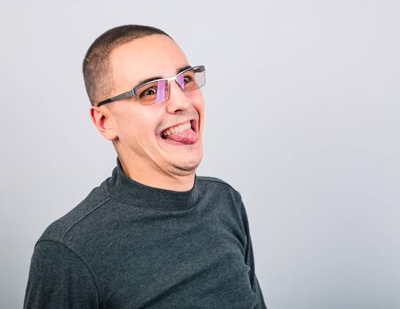Crazy grimacing man in eye glasses showing the tongue on blue background. Closeup portrait 写真素材