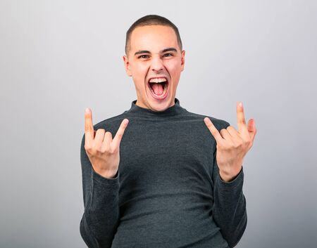 Crazy grimacing man showing the rock sign by two hands with crying open mouth on blue background with empty copy space. Closeup portrait