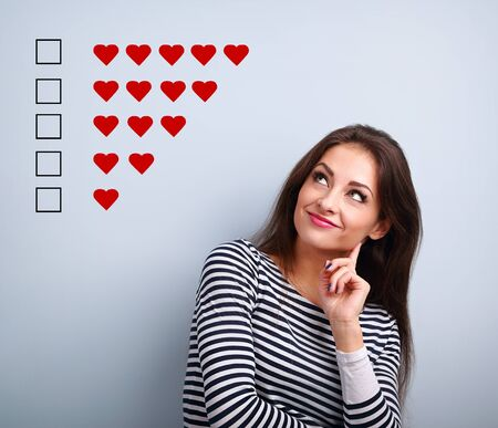 Thinking smiling young woman looking up and voting on five red hearts ranking on blue background with empty copy space. Closeup
