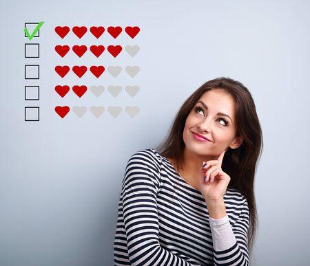 Denkende lächelnde junge Frau, die nach oben schaut und über fünf rote Herzen abstimmt, die auf blauem Hintergrund mit leerem Kopienraum rangieren. Nahaufnahme Standard-Bild