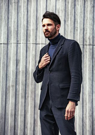 Fashion beard style business handsome man posing in style jacket on street wall outdoors background. Closeup .