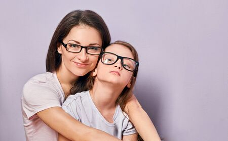 Happy young casual mother and smiling and hugging her kid in fashion glasses on purple background with empty copy space. Closeup