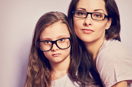 Happy young casual mother and serious sad kid in fashion glasses hugging on purple background with empty copy space. Closeup toned portrait