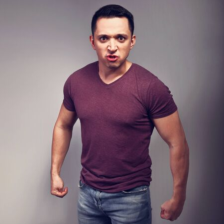 Angry man in casual t-shirt and blue jeans with negative emotion looking with fists on grey background. Toned. Angry jealous husband concept