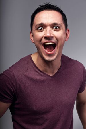 Angry excited man shouting the wide opened mouth. Closeup emotion bright portrait
