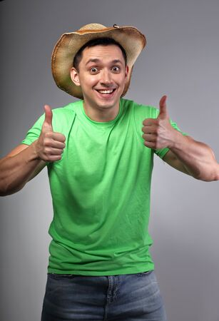 Happy smiling young man in hat showing thumb up by two hands in green summer shirt on grey background. Closeup