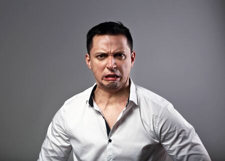 Pout grimacing angry business man looking aggressive on grey background. Closeup emotion portrait Stockfoto