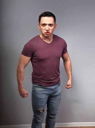 Angry man in casual t-shirt and blue jeans with negative emotion looking with fists on grey background.