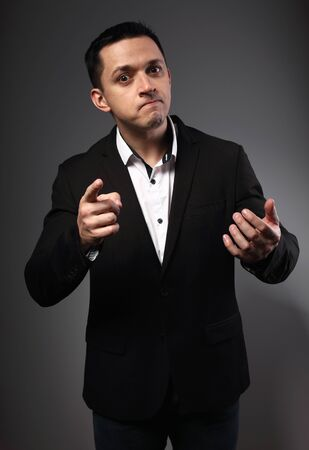 Surprising grimacing man looking in black suit with funny face showing the finger on grey studio background. Closeup actor portrait.