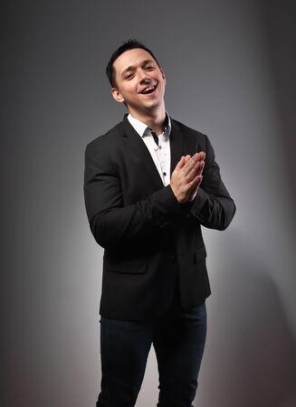 Gelukkig lachend vol energie opgewonden jonge zakenman in zwart pak klappen in de handpalmen op grijze donkere achtergrond met lege kopie ruimte. Close-up portret Stockfoto