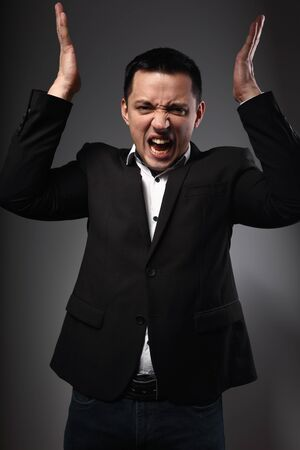 Angry business man in suit loud screaming with wide open mouth and gesturing the hands on grey background. Closeup emotion portrait