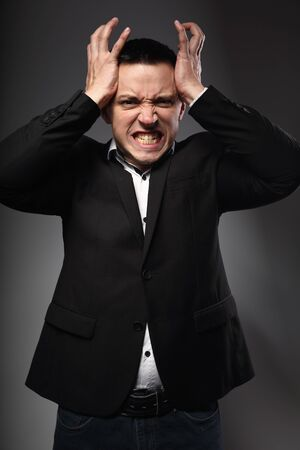 Angry business man in suit holding the head the hands on grey background. Closeup emotion portrait