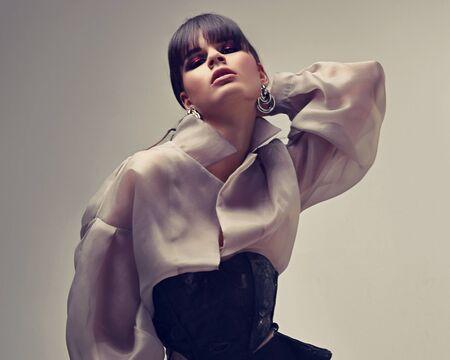 Incroyable belle femme asiatique avec un style de cheveux noirs bob stright et un maquillage lumineux du soir posant dans des vêtements en soie de mode sur fond gris. Portrait de studio doux couleur gros plan