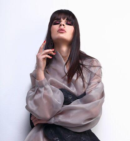 Incroyable belle femme asiatique avec un style de cheveux noirs stright bob posant dans des vêtements en soie de mode sur fond gris. Gros plan portrait en studio.