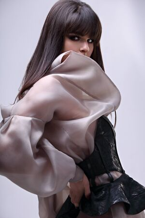 Amazing beautiful woman with bob stright black hair style in fashion silk clothing on gray background. Closeup portrait