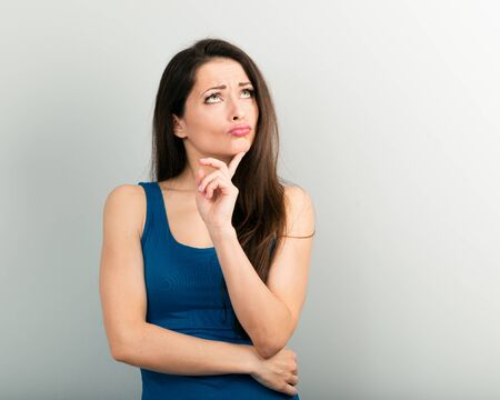Beautiful young angry unhappy woman with finger sign have an idea and looking up in casual blue shirt and long hair. Closeup portrait Stockfoto